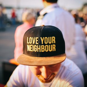 """Man wearing hat that reads """"Love Your Neighbor""""."""